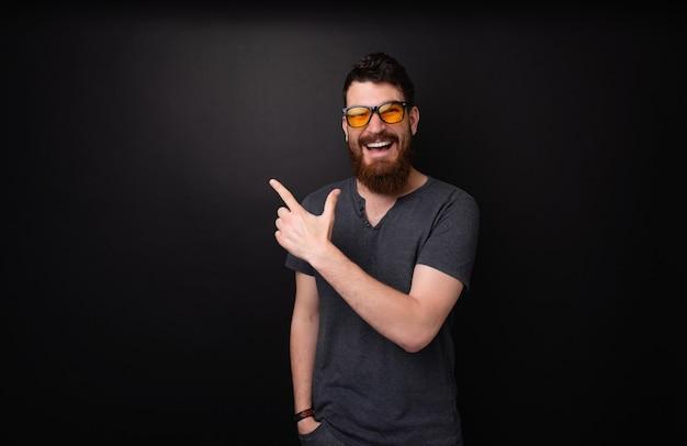 어두운 배경 위에 카메라를 보면서 멀리 가리키는 행복한 수염 난 남자의 사진