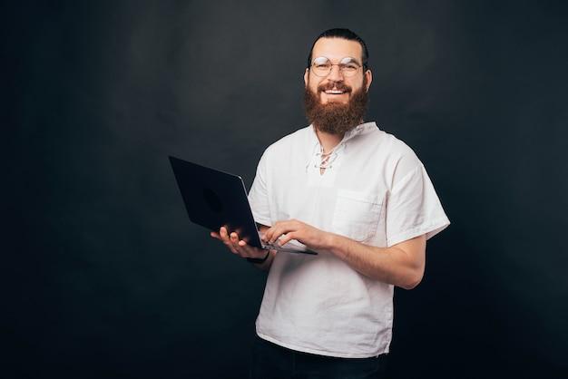 丸いメガネをかけ、黒い背景の上にラップトップを使用して幸せなひげを生やした流行に敏感な男の写真