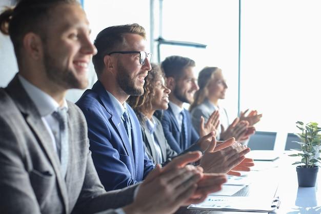 Фото счастливых деловых людей аплодируют на конференции.