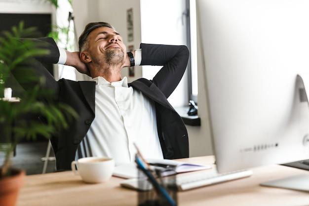 책상에 앉아 사무실에서 컴퓨터에서 작업하는 동안 웃고 양복을 입고 행복 사업가 30 대의 사진