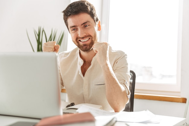 Фотография счастливого бизнесмена 30-х годов в белой рубашке, использующего ноутбук, во время работы в ярком офисе