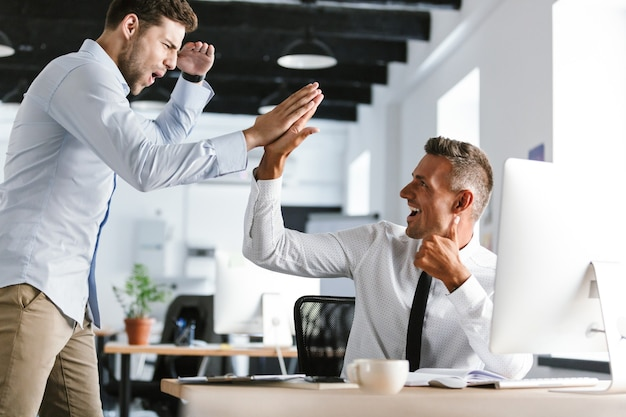 成功した取引中に、オフィスでハイタッチを一緒に与えるフォーマルな服を着た30代の幸せなビジネスマンの写真