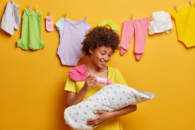 幸せな思いやりのある母親の写真は、乳児に授乳し、哺乳瓶からミルクを与え、母性の経験を積み、健康な新生児がいることを嬉しく思い、ポーズをとる