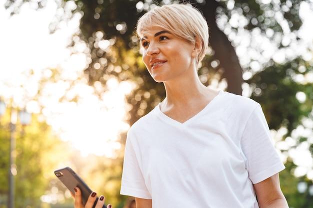 緑豊かな都市公園を散歩中にスマートフォンを持って笑顔でカジュアルな服を着て幸せな白人女性の写真