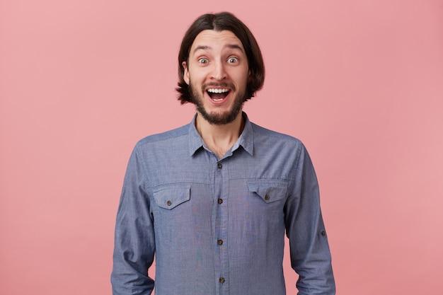 デニムシャツで長い櫛の黒髪をした幸せで陽気な驚いたひげを生やした若い男の写真は、良いニュースを聞いて、ピンクの背景の上に隔離された口を開けて喜んだ。