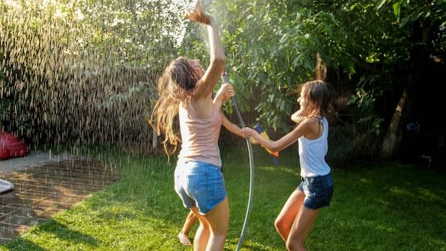 水庭のホースの下で踊ったりジャンプしたりする濡れた服を着た幸せな陽気な女の子の写真。夏に屋外で遊んで楽しんでいる家族