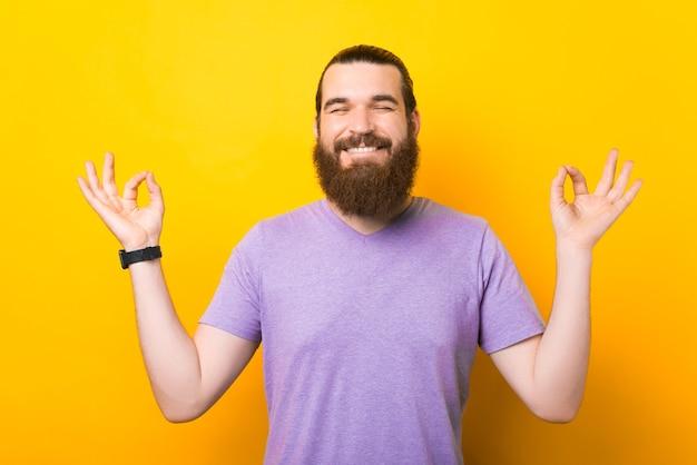 黄色の背景の上に立って禅のジェスチャーをし、瞑想している幸せな陽気な若いひげを生やした男の写真