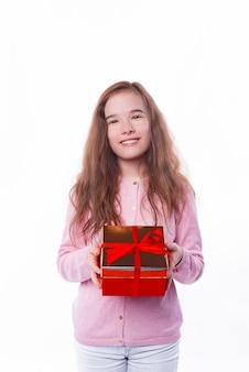 흰 벽에 빨간색 선물 상자를 들고 행복 한 아이 소녀의 사진