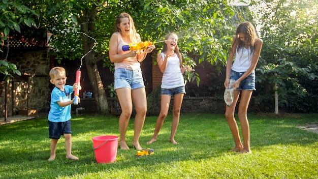 家の裏庭の庭で水鉄砲の戦いをしている幸せな子供たちの写真。夏に屋外で遊んで楽しんでいる家族