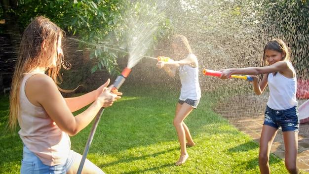Фотография счастливых детей, имеющих бой с водяным пистолетом в саду заднего двора дома. семья играет и развлекается на открытом воздухе летом