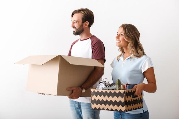 白い壁の上に隔離された脇を見ながら段ボール箱を保持しているカジュアルな服を着た幸せなカップルの写真