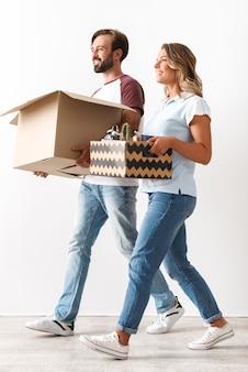 白い壁の上に孤立して歩いている間、段ボール箱を保持しているカジュアルな服を着て幸せなカップルの写真