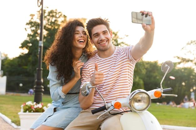도시 공원에서 오토바이에 함께 앉아있는 동안 휴대 전화에 셀카를 복용 행복한 커플의 사진