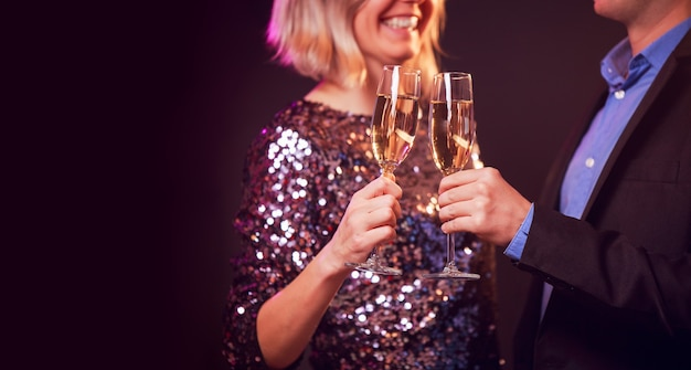 黒の背景にシャンパンとシャンパングラスと幸せなカップルの写真