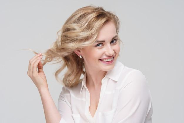 スタジオで白いシャツを着た幸せな巻き毛の女性の写真