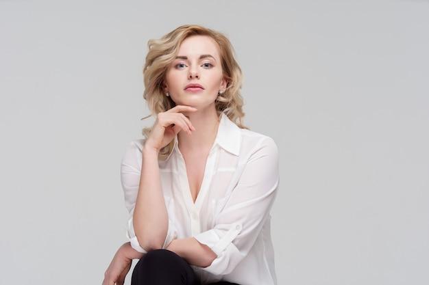 スタジオに座っている白いシャツを着た幸せな巻き毛の女性の写真