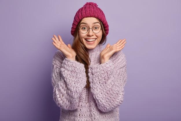 Фотография счастливой эмоциональной европейской женщины жестикулирует обеими руками, сжимает ладони, носит круглые очки, одета в зимнюю шапку, вязаный джемпер, изолирована на фиолетовой стене. концепция хороших эмоций.