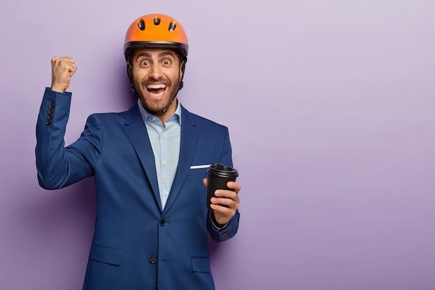 幸せなエンジニアの写真はコーヒーブレイクを持って、紙コップを持って、勝利で拳を握りしめ、嬉しそうに笑って、帽子とスーツを着ています