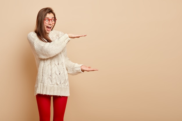 받은 선물 상자의 거대한 크기에 감동하는 행복 한 흥분된 여자의 사진은 양손으로 큰 제스처를 만듭니다