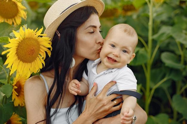 幸せな家族の写真。母と娘。ひまわり畑で一緒に家族。