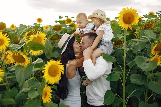 Фотография счастливой семьи. родители и дочь. семья вместе в поле подсолнечника. мужчина в белой рубашке.