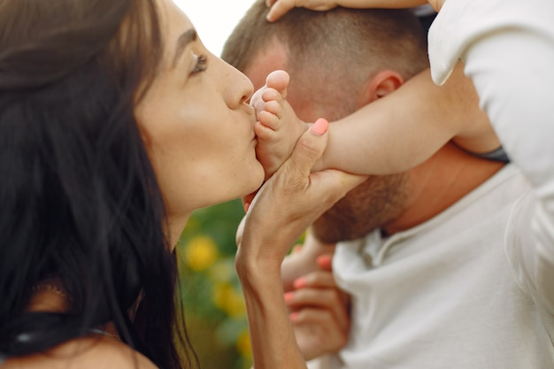 幸せな家族の写真。両親と娘。ひまわり畑で一緒に家族。白いシャツの男。