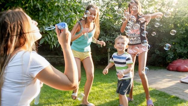 Фотография счастливой семьи, играя с мыльными пузырями в саду задворк дома. семья играет и развлекается на открытом воздухе летом