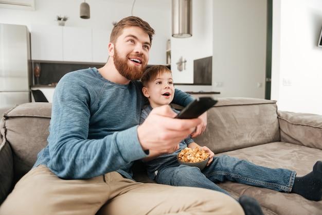 Фотография счастливого отца, держащего пульт дистанционного управления, во время просмотра телевизора с маленьким милым сыном, держащим попкорн.