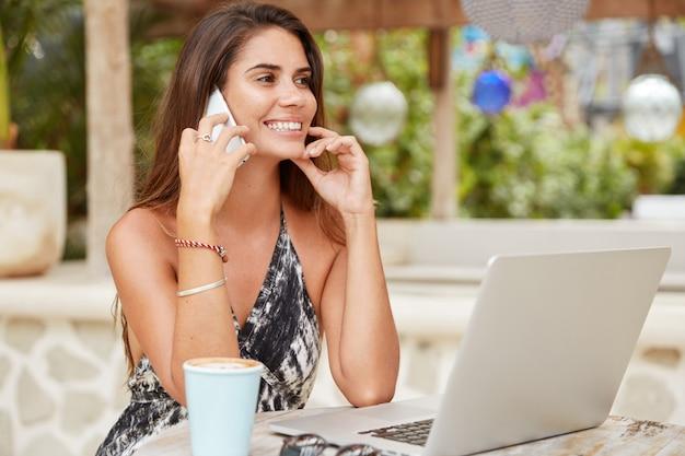 幸せな女性のフリーランサーの写真は、コーヒーを飲んだり、リゾート地で夏休みを過ごしたり、携帯電話で親戚と印象を共有したりします