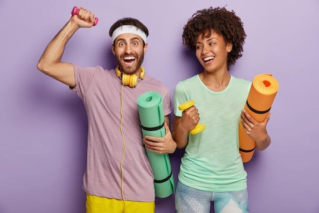 幸せな男女の写真は、ウェイトを使って上腕二頭筋に取り組み、カレマットを運び、楽しい表情を持ち、一緒にトレーニングを楽しみ、カジュアルな服を着て、健康的なライフスタイルとスポーツに動機付けられています