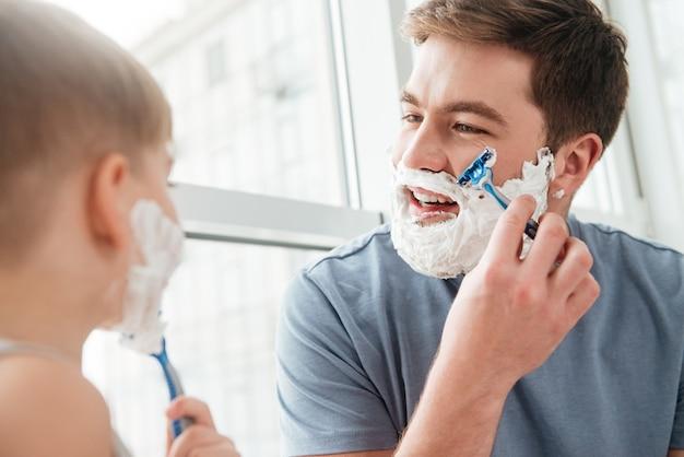 행복한 잘생긴 아버지와 아들의 사진이 얼굴에 면도 거품을 바르고 욕실에서 면도하는 동안 웃고 있습니다