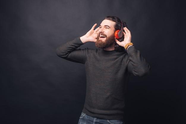Фотография счастливого красавца, слушающего музыку в наушниках над черной стеной