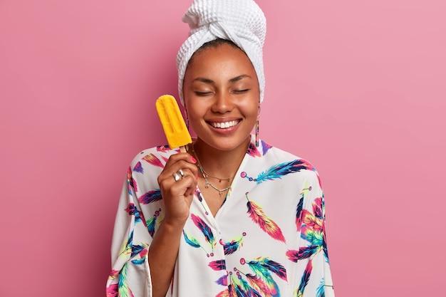 어두운 피부를 가진 행복한 건강한 여자의 사진은 눈을 감고 미소는 즐겁게 맛있는 아이스크림을 보유하고 있습니다.
