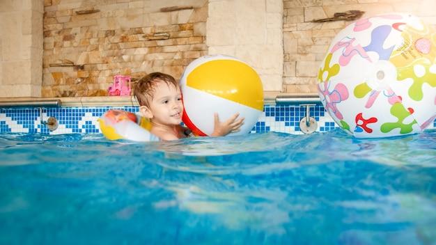 장난감을 가지고 놀고 실내 수영장에서 수영을 배우는 행복한 웃고 웃는 어린 소년의 사진