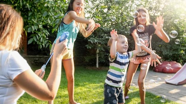 家の裏庭でシャボン玉を吹いて捕まえている幸せな笑っている子供たちの写真。夏に屋外で遊んで楽しんでいる家族