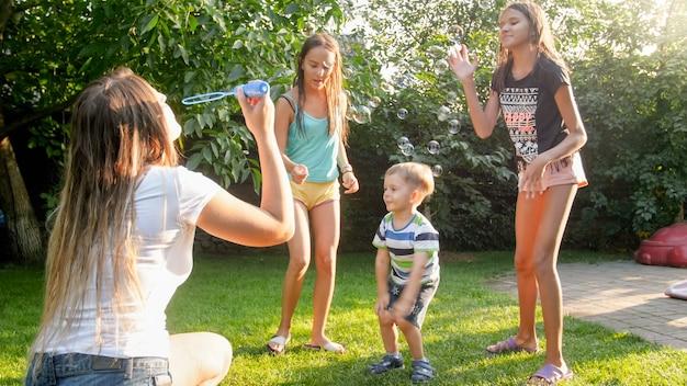 Фото счастливых смеющихся детей дуя и cathcing мыльные пузыри на заднем дворе дома. семья играет и развлекается на открытом воздухе летом