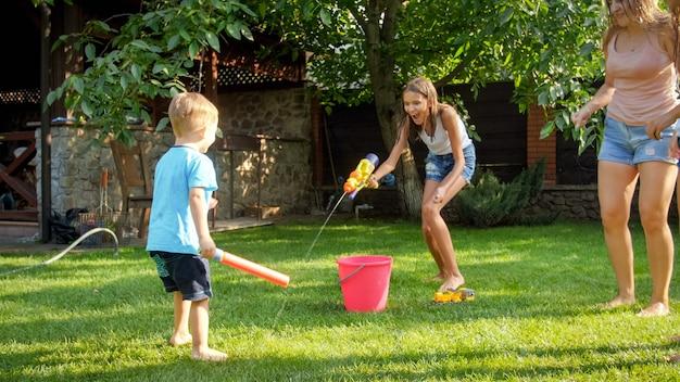 Фото счастливой смеющейся семьи брызгая водой с водяными пушками и садовым шлангом на заднем дворе. люди играют и веселятся в жаркий солнечный летний день