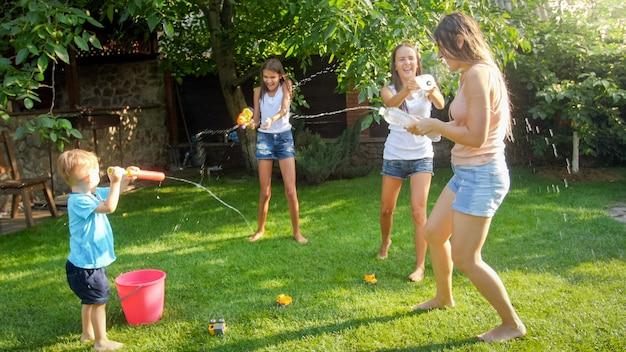 裏庭で水鉄砲と庭のホースで水をはねかける幸せな笑い家族の写真。暑い晴れた夏の日に遊んで楽しんでいる人