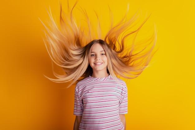 Фотография счастливой маленькой девочки со светлыми волосами, летящими на желтом фоне