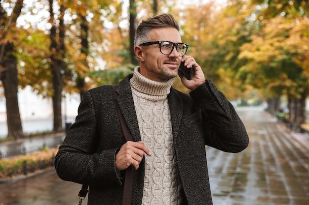 가을 공원을 걷는 따뜻한 옷을 입고 휴대 전화를 사용하는 행복한 사나이 남자 30 대 사진