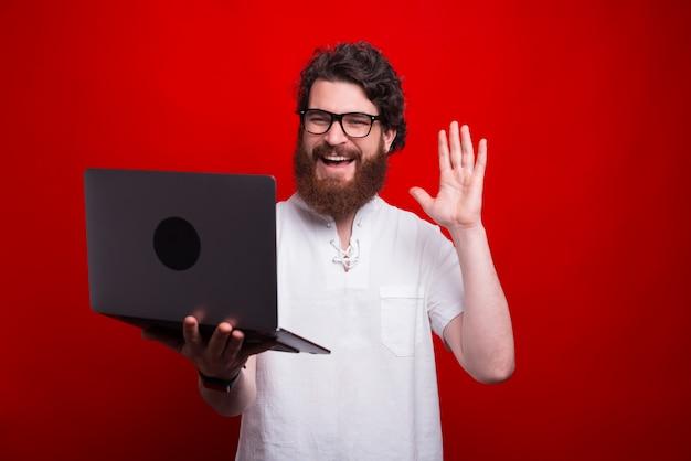ノートパソコンで誰かとオンラインで話していると敬礼幸せな男の写真