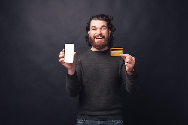 スマートフォンでクレジットカードと空の空白の画面を示すひげを持つ幸せな男の写真
