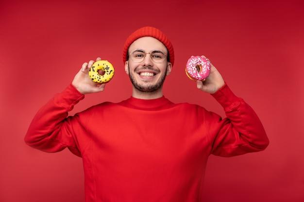 眼鏡と赤い服を着た素敵な笑顔とあごひげを持つ幸せな男の写真。赤い背景の上に隔離されたお菓子ドーナツを食べることをお楽しみください。