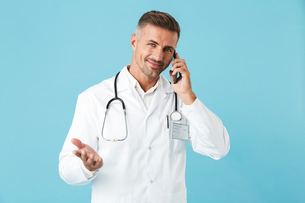 青い壁の上に孤立して立って、携帯電話で話している白衣と聴診器を身に着けている幸せな医師の写真