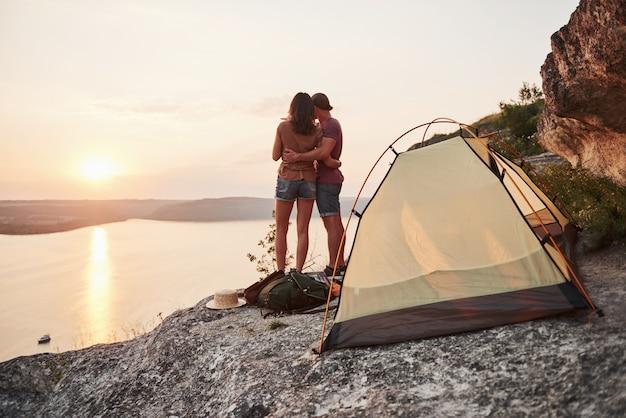 ハイキング旅行中に湖の景色を望む幸せな近くのテントの写真。旅行ライフスタイルの冒険休暇の概念