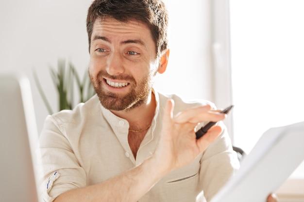 Фотография счастливого офисного работника 30-х годов в белой рубашке, использующего ноутбук и бумажные документы, сидя за столом на современном рабочем месте