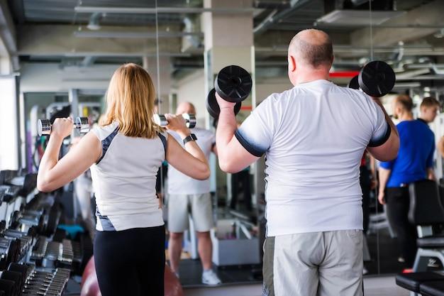 Фотография счастливой пожилой супружеской пары, делающей упражнения с гантелями. Premium Фотографии