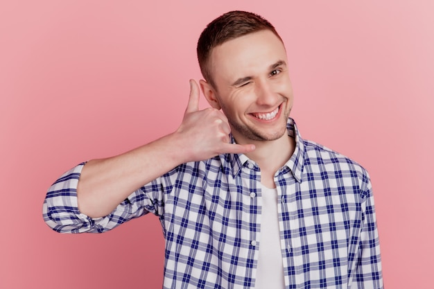幸せなポジティブな笑顔の男の写真は、ピンク色の背景に分離されたウィンクアイを教えてジェスチャー電話を呼んでください
