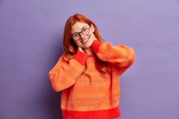 На фото счастливая рыжая женщина держит руки на шее и наклоняет голову, позитивно улыбается, носит прозрачные очки, а джемпер слышит что-то позитивное.