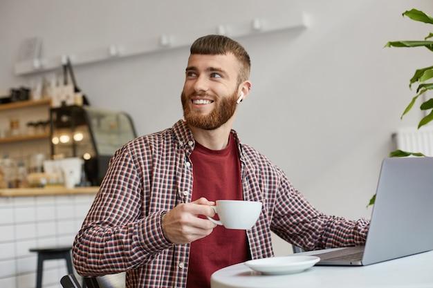 Фотография счастливого улыбающегося привлекательного рыжего бородатого мужчины, работающего за ноутбуком, сидящего в кафе, пьющего кофе, одетого в основную одежду, смотрящего вправо, спасибо бариста за чудесный кофе.